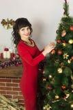 Dziewczyna w czerwonej sukni dekoruje choinki obraz stock