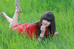 Dziewczyna w czerwonej sukni jest odpoczynkowa na zielonej trawie Obrazy Stock