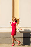 Dziewczyna w czerwonej sukni, okularach przeciwsłonecznych i kędzierzawym włosy, obrazy royalty free