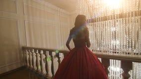 Dziewczyna w czerwonej sukni pozuje dla fotografa zbiory