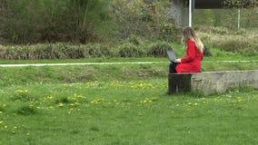 Dziewczyna w czerwonej sukni pracuje na ulicie z laptopem zbiory