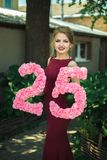 Dziewczyna w czerwonej sukni trzyma postać 25 Fotografia Royalty Free