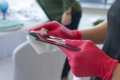 Dziewczyna w czerwonych rękawiczkach czyści talerza z zgłasza liczbę, przygotowywa dla ślubnego świętowania obrazy royalty free