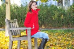 Dziewczyna w czerwonym żakiecie, siedzi na krześle Zdjęcia Royalty Free