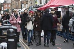 Dziewczyna w czerwonym berecie i mężczyzna z długie włosy w czarnym kapeluszu ubierał w chłodno londyńczyka stylu odprowadzeniu w Zdjęcia Stock