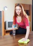 Dziewczyna w czerwonym cleaning stole z meblarskim połyskiem Zdjęcie Royalty Free
