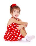 Dziewczyna w czerwonym kropki sukni obsiadaniu na podłoga Zdjęcia Stock