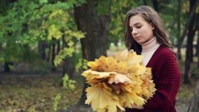 Dziewczyna w czerwonym poncho z bukietem żółci kwiaty, pozuje zbiory wideo