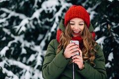 Dziewczyna w czerwonym zima kapeluszu, szaliku i używać smartphone i ono uśmiecha się zdjęcia royalty free