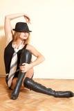 Dziewczyna w dźwigarka butach pozuje na tła wnętrzu kapeluszu i fotografia stock