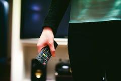 Dziewczyna w domowym środowisku, trzyma TV daleki Zdjęcie Stock