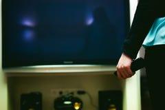 Dziewczyna w domowym środowisku, trzyma TV daleki Obrazy Stock