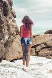 Dziewczyna w drelichowym kombinezonie na rockowej plaży Zdjęcia Royalty Free