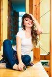 Dziewczyna w drelichowym spodniowym obsiadaniu na podłoga Fotografia Royalty Free