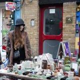 Dziewczyna w eleganckim kapeluszu sprzedaje rocznik szklane butelki na Ceglanym pasie ruchu Obraz Royalty Free