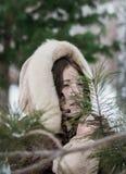 Dziewczyna w futerkowym żakiecie w zimie bawić się kryjówkę aport - i - zdjęcia stock