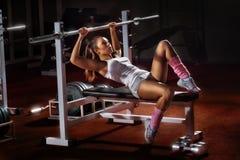 Dziewczyna w gym baru ławki prasie Obrazy Stock