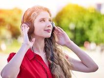 Dziewczyna w hełmofonach słucha muzyka w mieście obraz stock