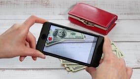 Dziewczyna w jej rękach trzyma smartphone, z którym strzela setki dolarowi rachunki i kiesy lying on the beach na zdjęcie wideo