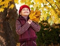 Dziewczyna w jesieni lasowy pozować, kolorów żółtych liściach i drzewach na tle, Obrazy Stock