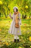 Dziewczyna w jesieni na spacerze w parków spojrzeniach przy spadać opuszcza fotografia royalty free
