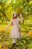 Dziewczyna w jesieni na spacerze w parków spojrzeniach przy spadać opuszcza obrazy royalty free