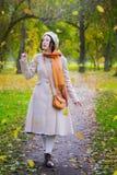 Dziewczyna w jesieni na spacerze w parków spojrzeniach przy spadać opuszcza zdjęcie stock