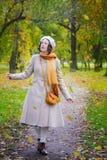 Dziewczyna w jesieni na spacerze w parków spojrzeniach przy spadać opuszcza zdjęcia stock