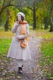 Dziewczyna w jesieni na spacerze w parków spojrzeniach przy spadać opuszcza fotografia stock