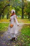 Dziewczyna w jesieni na spacerze w parków spojrzeniach przy spadać opuszcza zdjęcie royalty free