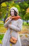 Dziewczyna w jesieni na spacerze w parków spojrzeniach przy spadać opuszcza obraz stock