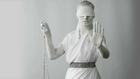 Dziewczyna w kamiennym statua kostiumu Femida bogini sprawiedliwość trzyma na białym tle w jeden ręce waży zbiory