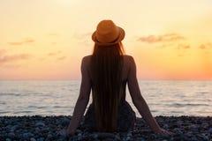 Dziewczyna w kapeluszowym obsiadaniu na seashore ujawnienia zawodnik bez szans zmierzchu czas sylwetka Obraz Royalty Free