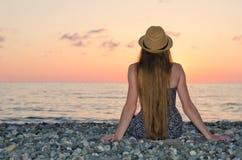 Dziewczyna w kapeluszowym obsiadaniu na seashore ujawnienia zawodnik bez szans zmierzchu czas widok z powrotem Fotografia Royalty Free