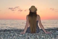 Dziewczyna w kapeluszowym obsiadaniu na seashore ujawnienia zawodnik bez szans zmierzchu czas widok z powrotem Zdjęcie Royalty Free