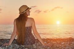Dziewczyna w kapeluszowym obsiadaniu na seashore ujawnienia zawodnik bez szans zmierzchu czas widok z powrotem Zdjęcia Stock