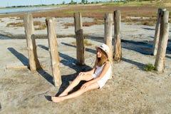 Dziewczyna w kapeluszowym obsiadaniu na ziemi Zdjęcie Stock