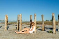Dziewczyna w kapeluszowym obsiadaniu na ziemi Obraz Stock