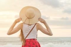 Dziewczyna w kapeluszowym patrzejący morze ujawnienia zawodnik bez szans zmierzchu czas widok z powrotem Obraz Royalty Free