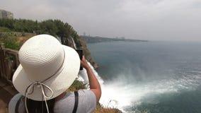Dziewczyna w kapeluszu bierze wideo bardzo piękna siklawa blisko morza zbiory wideo