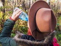 Dziewczyna w kapeluszu w jesień lasu napojów wodzie od butelki fotografia stock