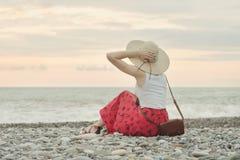 Dziewczyna w kapeluszu siedzi na otoczak plaży widok z powrotem ujawnienia zawodnik bez szans zmierzchu czas Zdjęcie Stock