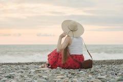 Dziewczyna w kapeluszu siedzi na otoczak plaży widok z powrotem ujawnienia zawodnik bez szans zmierzchu czas Obraz Royalty Free