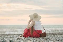 Dziewczyna w kapeluszu siedzi na otoczak plaży widok z powrotem ujawnienia zawodnik bez szans zmierzchu czas Zdjęcia Royalty Free