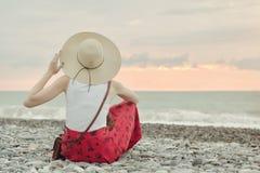 Dziewczyna w kapeluszu siedzi na otoczak plaży widok z powrotem ujawnienia zawodnik bez szans zmierzchu czas Zdjęcia Stock