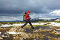 Dziewczyna w kapeluszu skacze nad garbkami wśród wody na śnieżnym gazonie Obrazy Stock