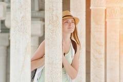 Dziewczyna w kapeluszu stojakach wśród marmurowych kolumn journeyer obraz stock