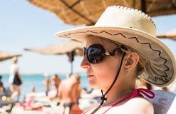 Dziewczyna w kapeluszu z ampułą odpowiada sunning na plaży Zdjęcie Stock