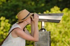 Dziewczyna w kapeluszy spojrzeniach w duże lornetki Park w tle Obrazy Stock
