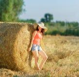 Dziewczyna w kapeluszy stojakach blisko sterty słoma i skrótach Zdjęcia Royalty Free
